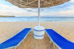 Paraplyet och två tomma deckchairs på kustsanden sätter på land Arkivfoto