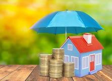 Paraplyskyddshuset myntar besparingar en affär Begrepp för hem för försäkring för skyddspengar arkivbild