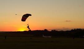Paraquedas da aterrissagem no por do sol foto de stock