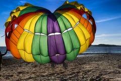 Paraquedas de Coulourfull na praia Fotografia de Stock Royalty Free