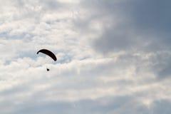 Paraquedas e silhueta humana Céu azul Fotos de Stock Royalty Free