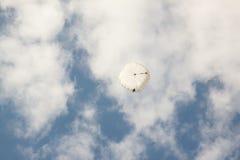 Paraquedas redondo branco no céu azul do fundo com nuvens Fotos de Stock