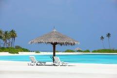 Parasóis na praia de Maldivas Foto de Stock