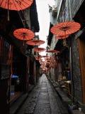 Parasóis vermelhos que penduram sobre a aleia em China imagens de stock royalty free