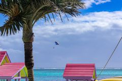 A parasail floats past the colorful roofs of San Pedro next to the blue and azure waters of the Caribbean Sea off of the coast of Stock Image