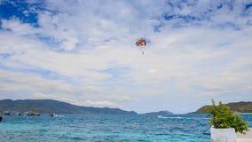 Parasailer comienza a volar de la playa sobre el mar contra el cielo en la isla almacen de metraje de vídeo
