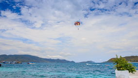 Parasailer starts fly from beach over sea against sky on island. NHA TRANG, KHANH HOA/VIETNAM - SEPTEMBER 11 2015: Parasailer starts to fly from beach over azure stock video footage