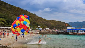 Parasailer takes off flies from beach into blue sky on island. NHA TRANG, KHANH HOA/VIETNAM - SEPTEMBER 11 2015: Parasailer takes off from beach and flies over stock video