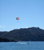 Parasailer in Zihuatanejo. Parasailer enjoys the view as the boat their attacted to race around in Zihuatanejo, Mexico Royalty Free Stock Photography