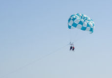 Parasailing. Couple parasails high above the blue waters Royalty Free Stock Photos