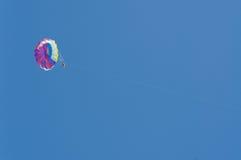 Parasailing. Man parasails high above the blue waters Stock Image