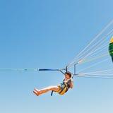 Parasailing da menina no paraquedas no céu azul Fotografia de Stock Royalty Free