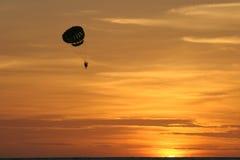 Parasailing dans le coucher du soleil d'or Images stock