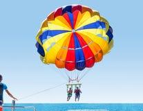 Parasailing de sorriso feliz dos pares na praia tropical no verão Recém-casados sob o meio do ar de suspensão do paraquedas Tendo fotos de stock