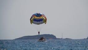 Parasailing detrás del inmigrantes en pateras de las moscas sobre el mar en un paracaídas almacen de metraje de vídeo
