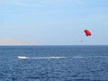Parasailing in Egypt side view from afar. Red parachute Royalty Free Stock Photo