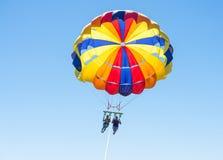 Parasailing feliz de los pares en playa Dominicana en verano Pares debajo del paracaídas que cuelga el mediados de aire Padre y n Foto de archivo libre de regalías