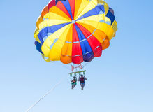 Parasailing feliz de los pares en playa Dominicana en verano Pares debajo del paracaídas que cuelga el mediados de aire Padre y n Imagen de archivo