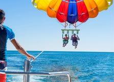 Parasailing feliz dos pares em Miami Beach no verão Pares sob o meio do ar de suspensão do paraquedas Tendo o divertimento Paraís fotos de stock