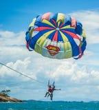 Parasailing. Happy young couple parasailing behind a boat in Rayong, Thailand Royalty Free Stock Image