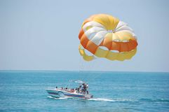 Parasailing launch. A parasailer prepares to be lifted off the boat stock images