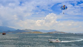 Parasailing over azure sea boat makes tight turn against hills. Panorama of parasailing over azure sea boat makes tight turn against mountains and blue sky in stock video