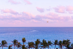 Parasailing over the ocean at sunset Stock Photo
