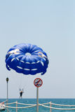 Parasailing over the water. Tourist attractions, flight on a parachute over the sea. sign on the pier, jump into the sea is prohibited Royalty Free Stock Image