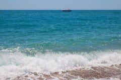 Parasailing speed boat near the rocky shore.  Royalty Free Stock Photography
