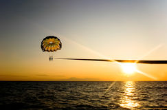 Parasailing during sunset. Royalty Free Stock Images