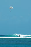Parasailing and surfing. A surfer catches a wave with a parasailer overhead Royalty Free Stock Photography