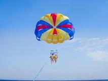 Parasailing in un cielo blu in spiaggia di Santorini Fotografia Stock