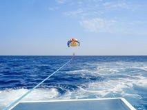 Parasailing in un cielo blu in spiaggia di Santorini Immagine Stock