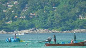 Parasailing, unsuccessful attempt, splashdown. PHUKET, THAILAND - NOVEMBER 19, 2015: A man and his parachute being removed from the water after splashdown stock video footage
