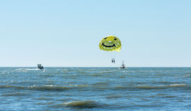 Parasailing on a yellow parachute over water Royalty Free Stock Photos
