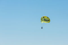 Parasailing on a yellow parachute over water Royalty Free Stock Image