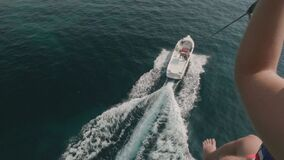 Parasailingswasserunterhaltung Fliegen auf einen Fallschirm hinter ein Boot in Montenegro stock footage