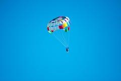 Parasailor στο πολύχρωμο αλεξίπτωτο που πετά στον μπλε σαφή ουρανό, ηλιόλουστος καιρός, εμπνευσμένος, καλοκαίρι, διακοπές Στοκ Εικόνες