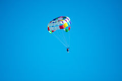 Parasailor on multi-colored parachute flying in blue clear sky, sunny weather, inspirational, summer, vacation. S, freedom stock images