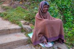 PARASHNATH, JHARKHAND, INDIEN 25. JANUAR 2017: Straßenporträt eines indischen Bettlers Dame, der auf der Seite einer Straße sitzt lizenzfreie stockfotos