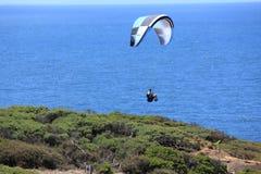 Parashoot die langs de kust vliegen Stock Afbeelding