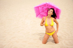 Parasol. Kneeing girl in swimsuit with pink parasol Royalty Free Stock Photos