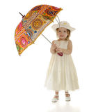 Parasol Baby. A dressed-up toddler carrying a bright, multi-colored parasol.  On a white background Royalty Free Stock Images