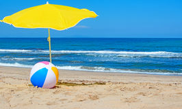 Parasol and ball. Beach ball under a yellow parasol by the shore Royalty Free Stock Photos