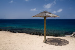 Parasol on the Beach. A small wooden parasol casts its shade on a sandy beach in Lanzarote, Spain stock images
