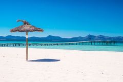 Parasol beach on the coast. White sand and blue water of the sea. Playa de Muro, Mallorca, Majorca, Spain