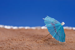 Parasol on beach sand with sea and blue sky Stock Photos