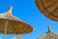Parasol on the beach in a sunny summer day over a blue sky background Royalty Free Stock Photos