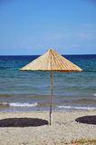 Parasol on the beach. Wooden parasol on the sandy beach Royalty Free Stock Image