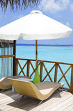 Parasol and chaise lounges on verandah of water vi Stock Photo